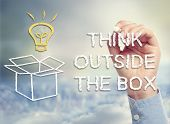 pic of thinking outside box  - Think outside the box concept with idea lightbulb and open box drawing in chalk - JPG