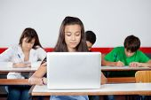 Teenage schoolgirl using laptop at desk with classmates in background
