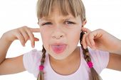 Little girl clogging her ears and wincing on white background