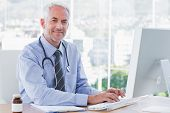 stock photo of antibiotics  - Doctor typing and using his computer in the office - JPG