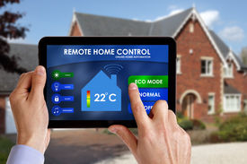 stock photo of controller  - Holding a smart energy controller or remote home control online home automation system on a digital tablet - JPG