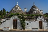 stock photo of conic  - Trulli houses with painted symbols on the conical roofs in Alberobello Italy - JPG