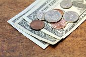 stock photo of spare  - spare change dollars and cents over wood background - JPG