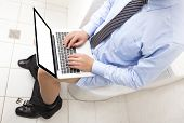 picture of farting  - businessman  working  in toilet with laptop - JPG