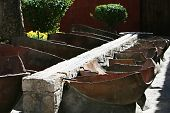 stock photo of trough  - Open air laundry in Santa Catalina Monastery Arequipa Peru. A Stone trough sends the water to wash tubs made of split amphorae