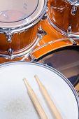 foto of drum-kit  - Two drumsticks on top of a drum kit - JPG