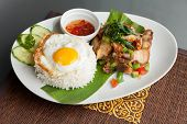 picture of crispy rice  - Traditional Thai dish crispy pork with a fried egg atop the jasmine rice served with chili sauce - JPG