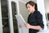 Woman At Home Reading Newspaper