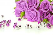 stock photo of purple rose  - Purple roses bouquet and beads on white background - JPG