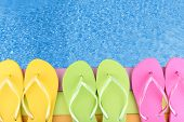 stock photo of beside  - Colored flip flops on wooden platform beside sea - JPG