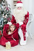 picture of saint-nicolas  - Little girl sits in Saint Nicolas bag - JPG