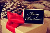stock photo of merry christmas text  - closeup of a box gift tied with red ribbon and a blackboard signboard with the text merry christmas and some pine cones in the background - JPG