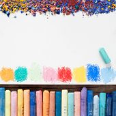 stock photo of pigment  - Pastel crayons and white paper sheet of sketchbook with spots of paints and pigment dust - JPG