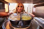 picture of oven  - Woman Putting TV Dinner Into Microwave Oven To Cook - JPG