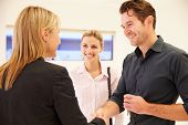 image of premises  - Estate Agent Shaking Hands With Clients In Empty Office - JPG