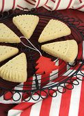 picture of shortbread  - Christmas shortbread triangle cookies on vintage baking rack on dark red rustic wood background with festive decorations - JPG