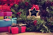 picture of merry christmas text  - a pile of gifts and a natural christmas wreath with pine cones and red berries - JPG
