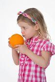 stock photo of fragrance  - little girl smells the fragrance of an orange fruit - JPG