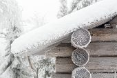 stock photo of laplander  - The wall and the edge of the roof of the hut covered with frost and snow on the background of a winter forest - JPG