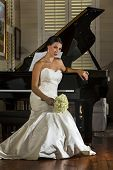 image of grand piano  - A modern bride poses indoors with a grand piano - JPG
