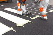 stock photo of pedestrian crossing  - Two workers making of a new pedestrian crossing on the road - JPG