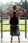 foto of crunch  - Muscular man doing crunches in outdoor gym in park - JPG