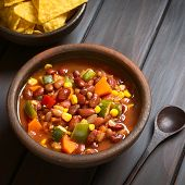 stock photo of kidney beans  - Rustic bowl of vegetarian chili dish made with kidney bean carrot zucchini bell pepper sweet corn tomato onion garlic with tortilla chips above photographed with natural light  - JPG