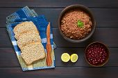 pic of kidney beans  - Overhead shot of wholegrain bread slices on dish towel with rustic bowl of homemade red kidney bean spread and raw red kidney beans photographed on dark wood with natural light - JPG