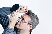 stock photo of dandruff  - Guy checking out his hair with a mirror - JPG