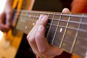 pic of fret  - kid playing a guitar focus on the hand holding the fretboard