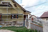 stock photo of insulator  - Construction or repair of the rural house fixing facade insulation and using color for new look - JPG