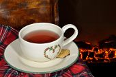 picture of cozy hearth  - A cup of tea by the fireplace in a cold winter night - JPG