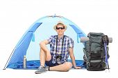 image of camper  - Studio shot of a male camper sitting in front of a blue tent with a backpack beside him isolated on white background - JPG