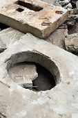 image of manhole  - Concrete block with the manhole opening on the pile of damaged concrete blocks - JPG