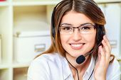 stock photo of telemarketing  - Friendly smiling young woman surrort phone operator at her workplace in the office - JPG