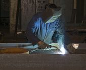 pic of tig  - Working man with helmet shield on his head is welding steel construction - JPG