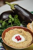 stock photo of arabian  - Traditional arabian eggplant dip baba ganoush with herbs and smoked paprika on a wooden background  - JPG