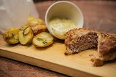 image of beef-burger  - Succulent cooked beef burger with potato on a wood plate. ** Note: Shallow depth of field - JPG