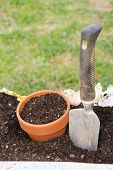 image of trowel  - Ceramic pot and a trowel in a bag of topsoil - JPG