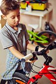 pic of adolescent  - Adolescent boy looking at bicycle - JPG