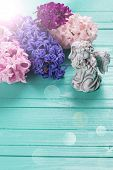 stock photo of blue angels  - Background with angel and fresh pink violet blue hyacinths in ray of light on painted wooden planks - JPG