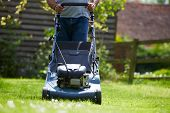 stock photo of grass-cutter  - Close Up Of Man Working In Garden Cutting Grass With Mower - JPG