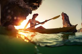 pic of kayak  - Young lady paddling the kayak in a bay with limestone mountains - JPG