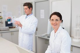 foto of beaker  - Scientist working attentively with laptop and another with beaker in laboratory - JPG