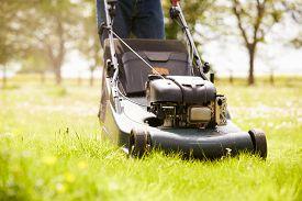 foto of grass-cutter  - Close Up Of Man Working In Garden Cutting Grass With Mower - JPG