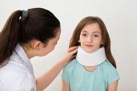 stock photo of neck brace  - Female Doctor Examining Neck Of Patient Wearing Neck Brace - JPG