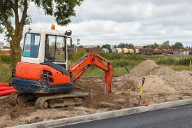 picture of excavator  - An excavator in a road construction site - JPG