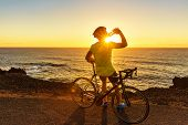 Biking Athlete cyclist man drinking water after intensive biking training, enjoying sunset and ocean poster
