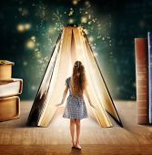 Adventure story and fairy tale. Tiny girl and book with magic glowing on table poster
