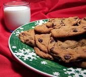 picture of christmas cookie  - Color photo of fresh hot chocolate chip cookies served on a green plate with white snowflakes around the rim - JPG